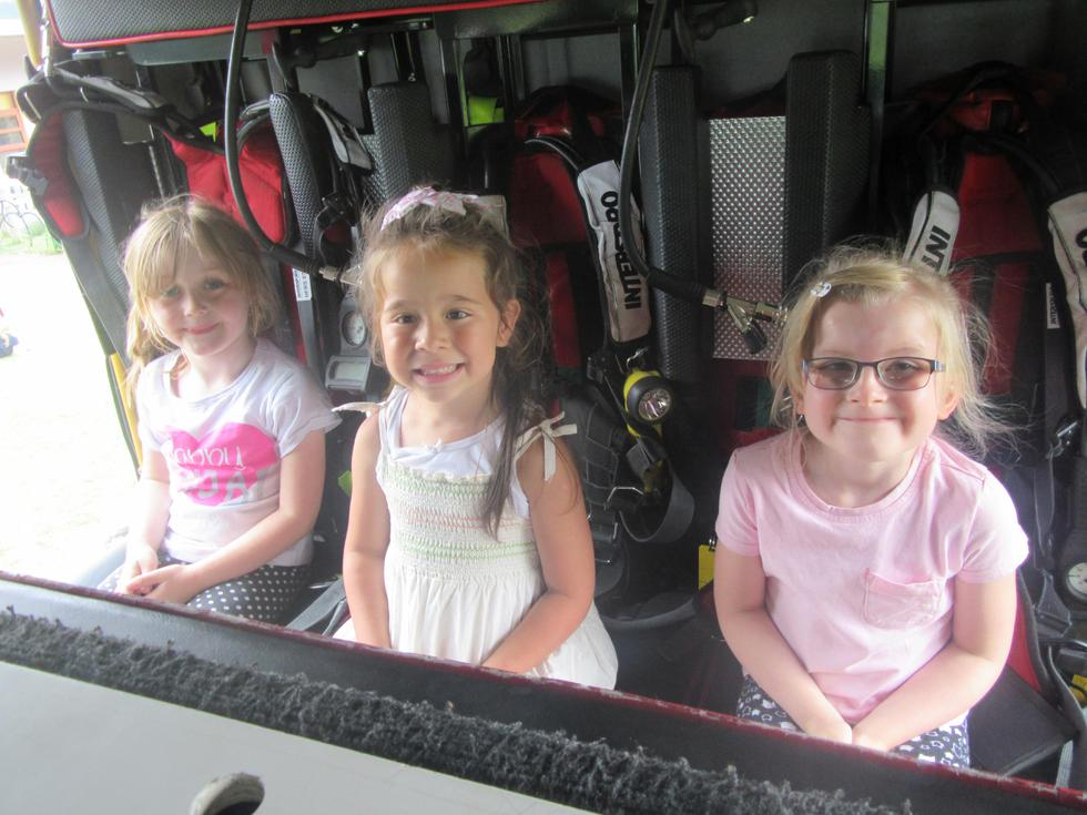 Isabella, Delia and Elouise sitting in the fire engine.JPG