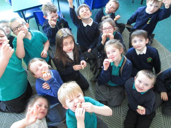 Our children trying hot cross buns during an RE assembly on Easter Foods.