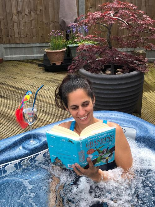 Mrs Valentine relaxing in her hot tub reading.