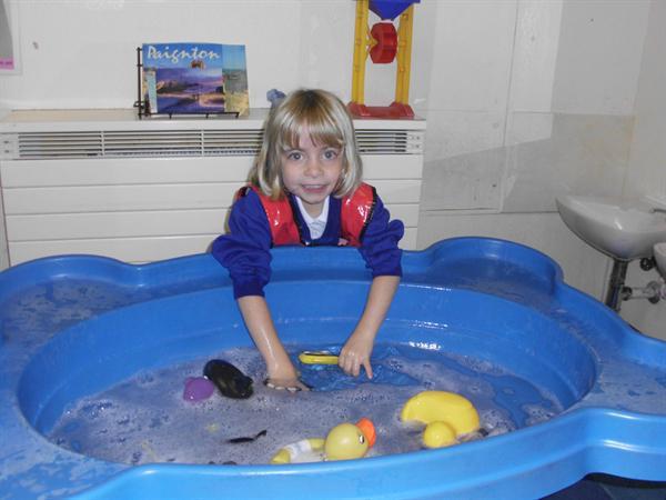 Katie raced the ducks in the water.