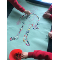 A group of children worked together and shared the buttons to make the skeleton.