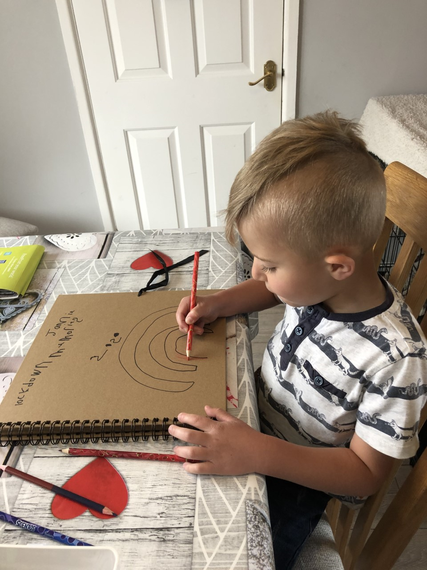 Busy drawing in his scrapbook