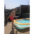 Having a dip in his paddling pool.