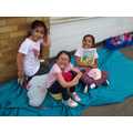 Year 2 children enjoying a book in the shade!