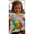 Cora is all smiles with her dinosaur book!