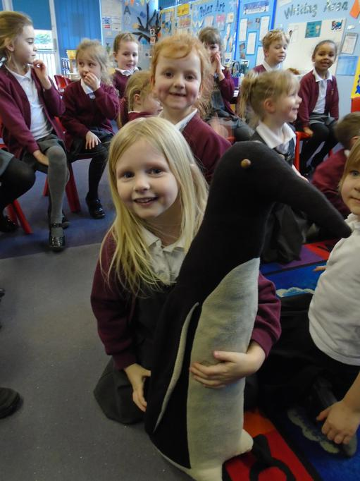 Holding a model of a penguin