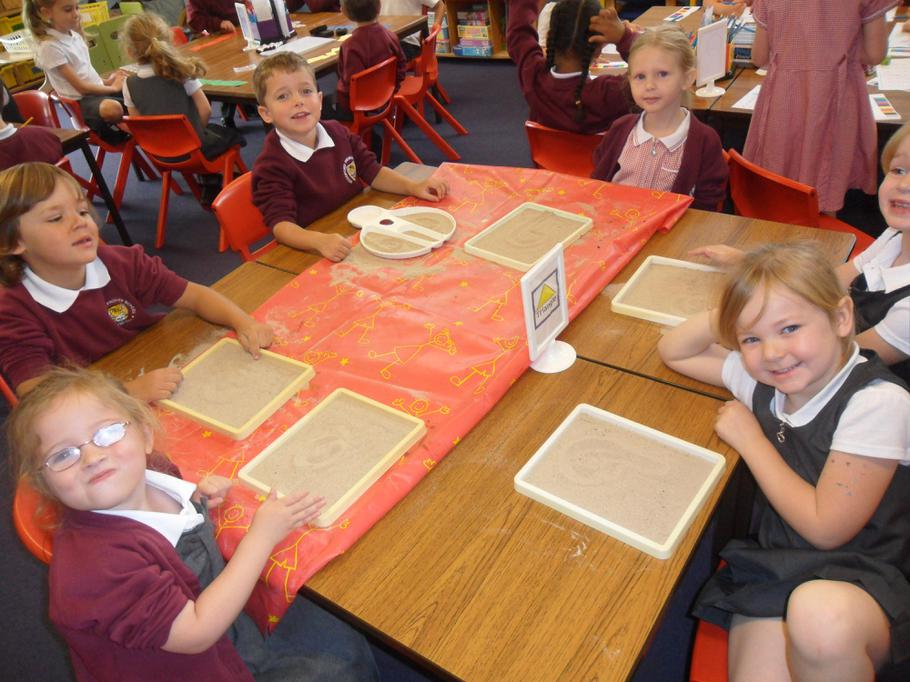 Practising writing numbers 0 - 10 in sand.