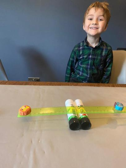 A exploring weight with his home made balance scales