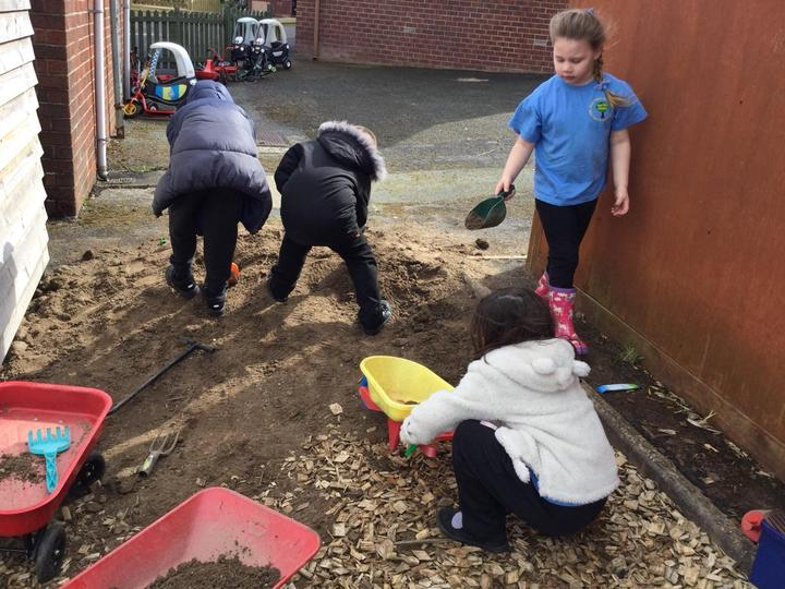 Working hard to move the top soil into our planters