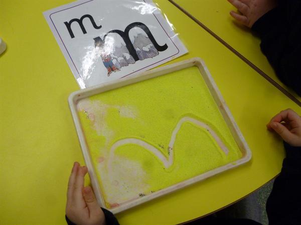 "Using sand to write ""m"""