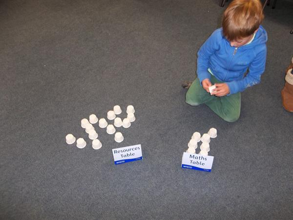Oliver has chosen to practise maths using cups!