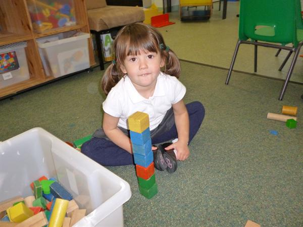 Using the wooden blocks to build towers.