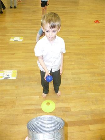 PE- using balls and aiming into a pot.