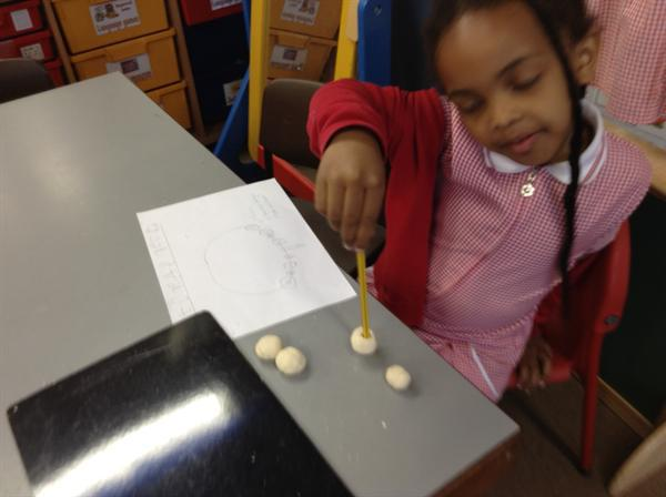 Making holes in our beads ready to thread.