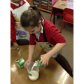 Making pancakes! Measuring milk.
