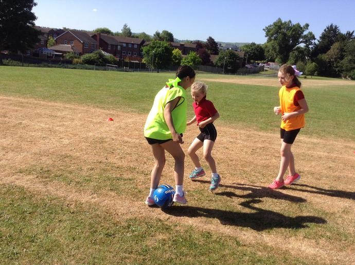 Children playing football and working together