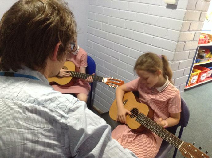 Children having guitar lessons.